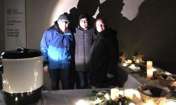 Vorstand am dekorierten Tisch, drei Personen hinter Ausschanktisch